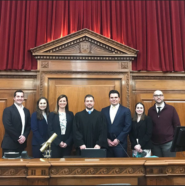 Photo of Mike with the winning mock trial team and their coaches